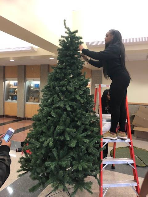 Cheerleaders setting up holiday trees